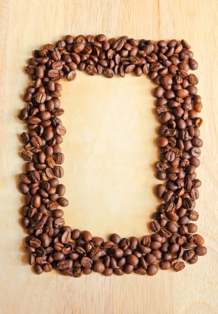 Coffee beans as frame with old paper for notes on the wooden background photo