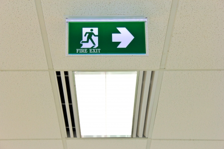 fire exit sign: Fire exit sign on ceiling with light Stock Photo