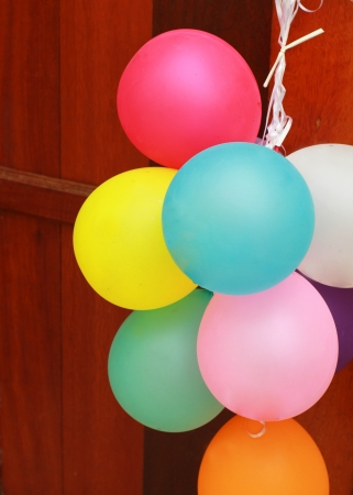 Multicolored balloons hanging on wooden door photo