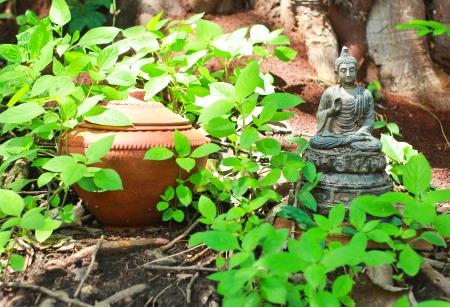 statute: Buddha statue with pot in garden Stock Photo
