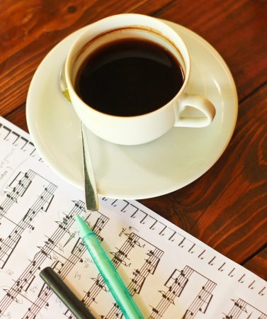 Hot coffee on music note with pen photo