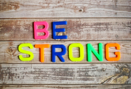 strong: Be strong in colorful plastic letterpress on wood background Stock Photo