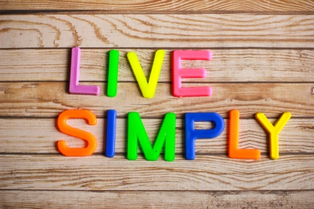 ifestyle: Live simply in colorful plastic letterpress on wood background Stock Photo