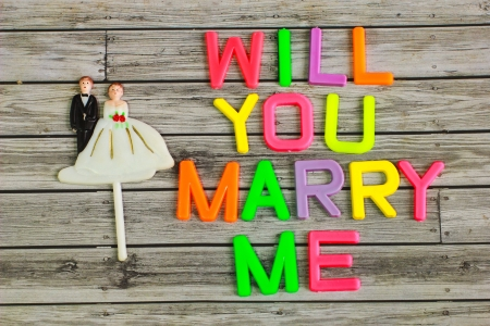 will you marry me: wedding bride and groom couple doll with will you marry me colorful plastic letterpress Stock Photo