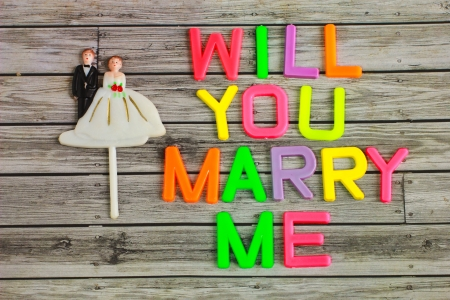 marry: wedding bride and groom couple doll with will you marry me colorful plastic letterpress Stock Photo