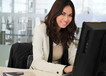 使用計算機年輕的亞洲女商人 版權商用圖片