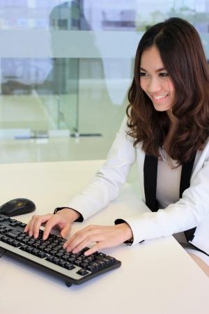 Joven y bella mujer de negocios asiáticos que usan una computadora