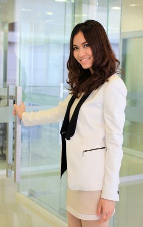 문 여는 비즈니스 아시아 여자 사무실에 오는