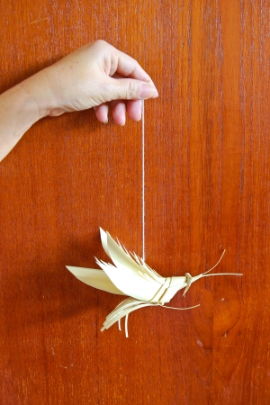 woman hanging toy: folded model grasshopper with hand