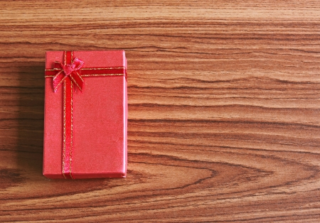 Red present box on wooden background  photo
