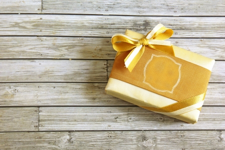 Gold present box on wooden background