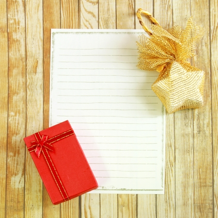 Present box and star with blank note paper on wooden background  photo