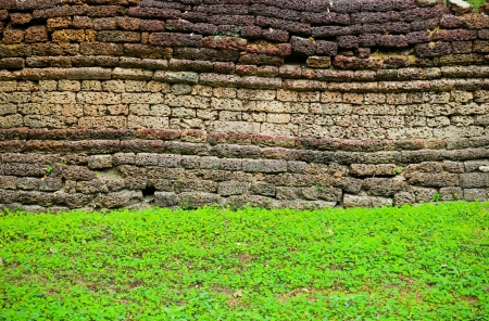 Texture of rough brick wall with grass photo