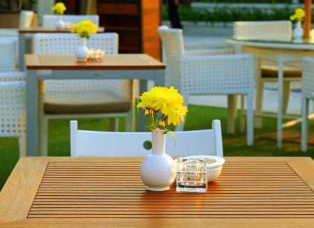 Stůl a židle nastavení s květinou v venkovní restaurace