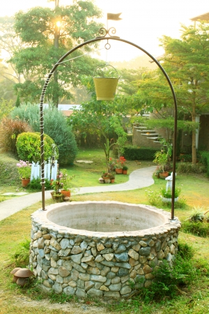 Old Well with a bucket in beautiful garden photo