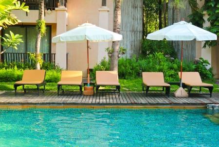 Strandstoelen en parasols kant zwembad