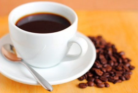White cup of coffee with coffee beans photo
