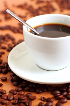 Cup of coffee with coffee beans and spoon photo