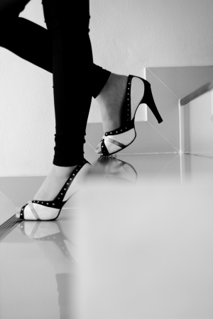 Female legs in high heels walking down stairs, black and white photo photo