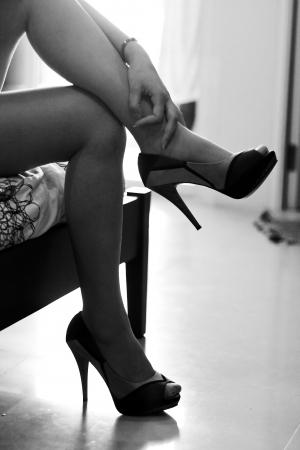 tacones negros: Piernas de mujer con tacones altos, foto blanco y negro Foto de archivo