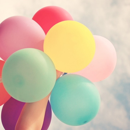 entertainment event: Hand holding multicolored balloons with retro filter effect Stock Photo