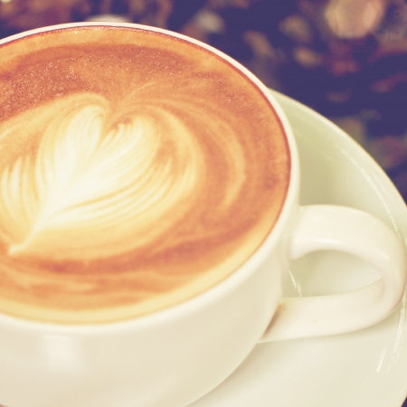 Cappuccino or latte coffee with heart shape, retro filter effect