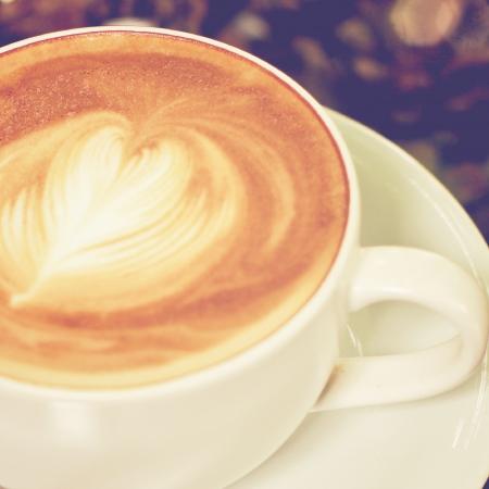 Capuchino o café con leche con forma de corazón, efecto de filtro retro
