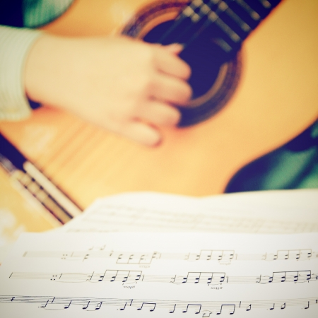 Musician playing classical guitar with musical chords, retro filter effect Stockfoto