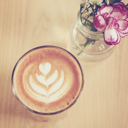 Cup of art latte or cappuccino coffee with flower, retro filter effect photo