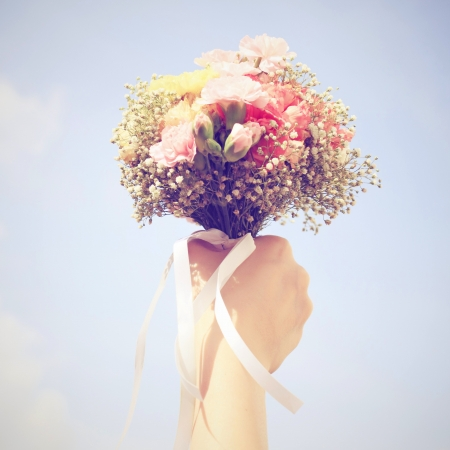 Boeket van bloemen in de hand en de blauwe hemel met retro filtereffect
