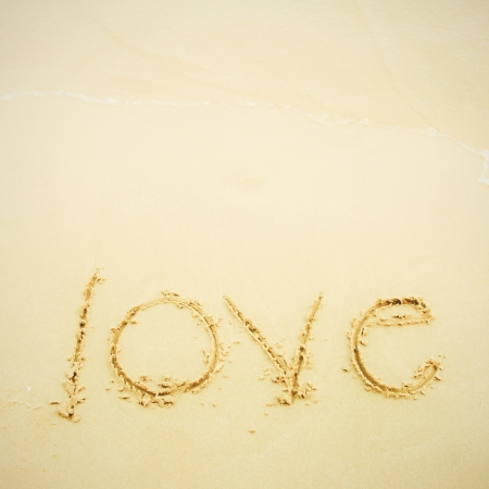 Hand written love on sand and beach photo