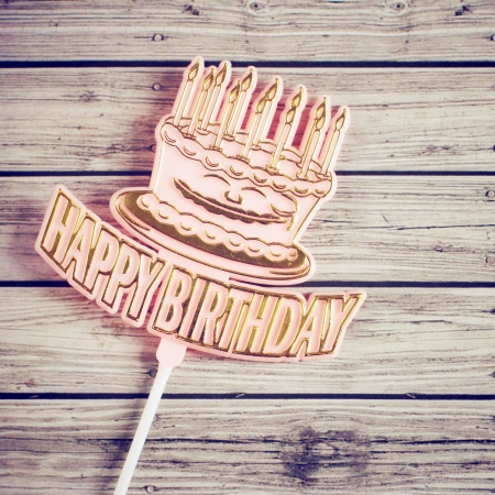 Happy birthday on wooden background with retro filter effect photo