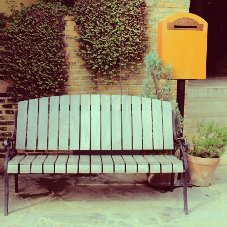 Wooden chair with vintage mailbox in garden, retro filter effect photo