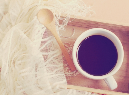 Silk scarf with black coffee and spoon on wooden tray, retro filter effect photo