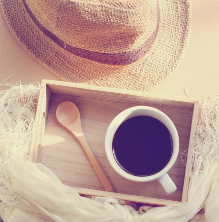 Straw hat with black coffee and spoon on wooden tray, retro filter effect Stock Photo - 24201424