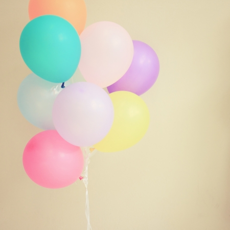 Colorful festive balloons on wall with retro filter effect