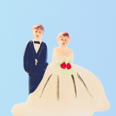 doll: Groom and bride couple doll on wedding cake Stock Photo