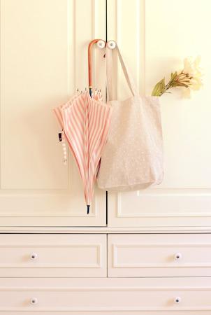Зонтик и большая сумка висит на старинных шкаф с ретро эффект фильтра