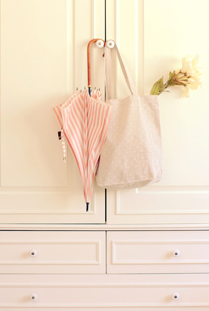 Umbrella and tote bag hanging on vintage wardrobe with retro filter effect