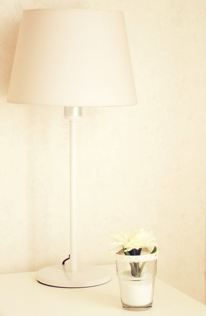 Lamp and flower on the table near bed with retro filter effect  photo