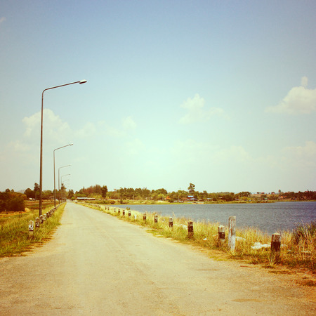 Road on reservoir with retro filter effect photo