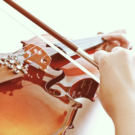 Woman playing violin with retro filter effect photo