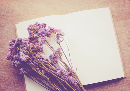 Blank notebook and dried statice flowers with retro filter effect photo