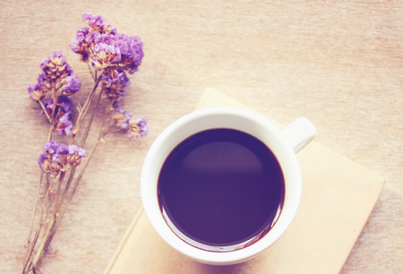 Black coffee on notebook with statice flowers, retro filter effect photo