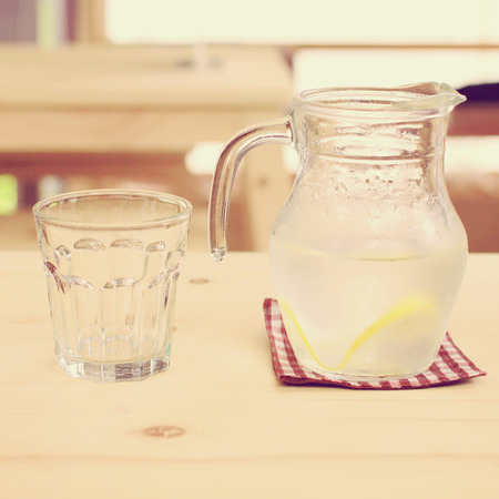 Jar of lemonade with empty glass for summer, retro filter effect photo