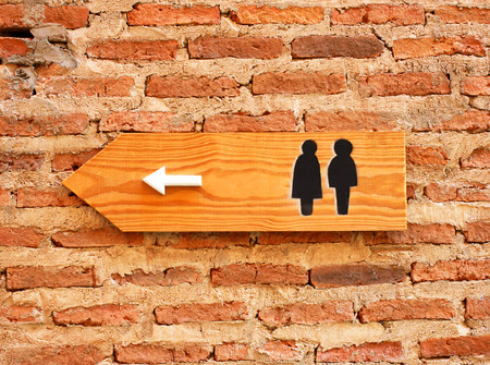 urinating: Toilet sign and direction on brick wall
