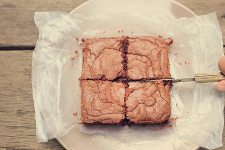 homemade style: Cutting crispy homemade brownie with retro filter effect
