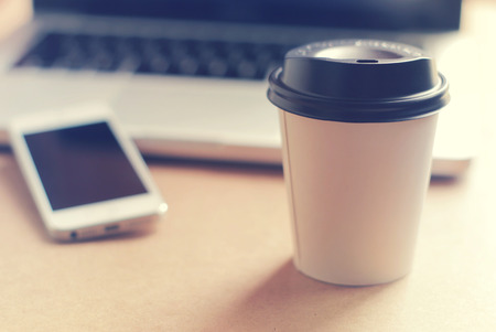 freelance: Coffee cup and smart phone with notebook computer, retro filter style toned Stock Photo