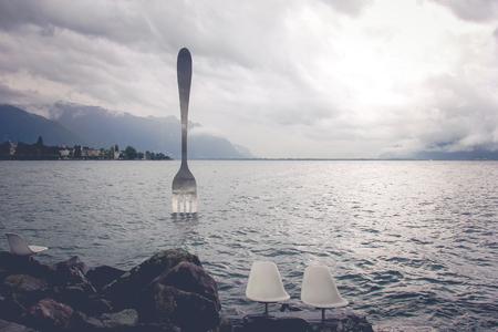 vevey: Vevey, Switzerland - AUGUST 13,2014: Giant steel fork in water of Geneva lake, Vevey, Switzerland. Stock Photo