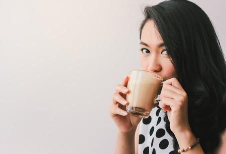 Mujer de tomar café con leche caliente en el café